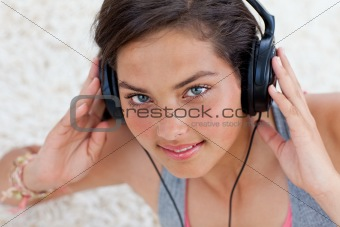 Charming teen girl listening to music on the floor