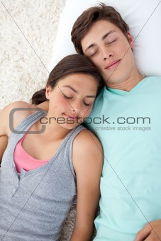A couple of teenagers sleeping on the floor with heads together