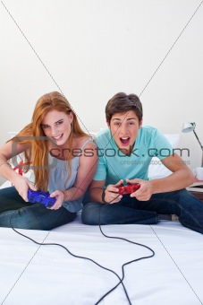 A excited teen couple playing video games