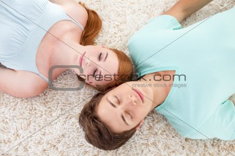 A couple of teenagers sleeping on the floor