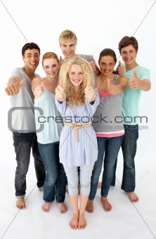 Group of teenagers standing in front of the camera with thumbs u