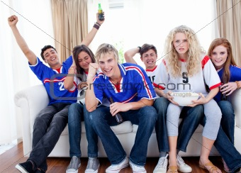 Excited and happy teenagers watching a football match in the living-room