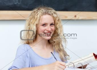 Smiling blonde teenager doing homework
