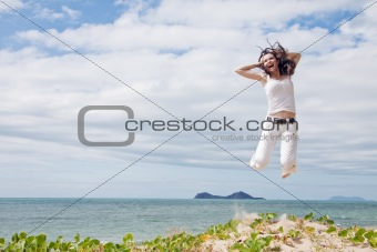 Attractive woman jumping of joy on tropical beach