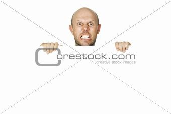 Angry man peeking over a wall
