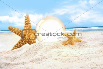 Crystal ball with starfish in the sand