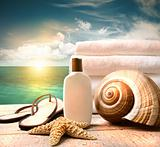 Sunblock lotion and towels and ocean scene