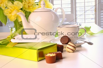 Box of chocolates on table with tea set