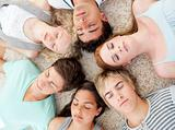 High angle of teenagers with their heads together sleeping on th