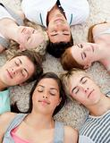Teenagers with their heads together sleeping on the ground 