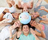 Teenagers on the floor with a terrestrial globe in the center an