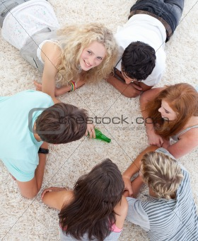 Group of teenagers playing spin the bottle on the floor