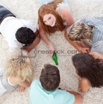 Group of friends playing spin the bottle on the floor