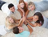 Friends lying on the floor with hands together