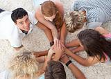 Teenagers lying on the ground with hands together