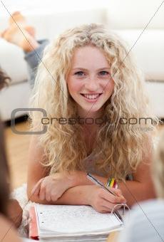 Beautiful teenager studying on the floor