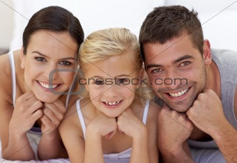 Cute little girl with her parents lying on a bed