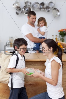 Smiling mother giving school lunch to her son