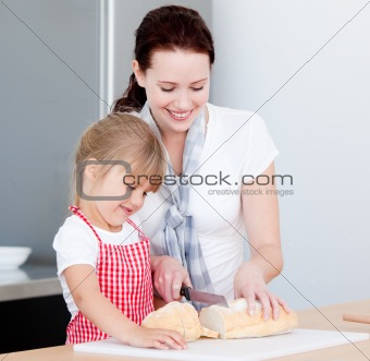 Mother teaching daughter how to cut bread in kitchen