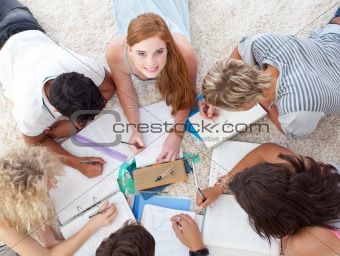 Group of cute Teenagers lying on the ground studying together
