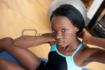 Beautiful woman in gym outfit doing sit-ups