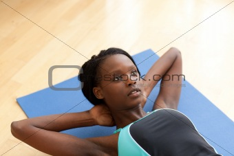 Charming woman in gym clothes doing sit-ups