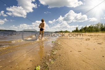 young boy running at the beautiful beach