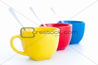 three colorful tea cups with spoons