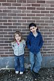 Young children hanging out near a grungy wall