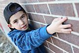 Young child hanging out near a grungy wall