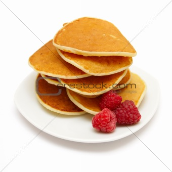 small pancakes topped with berries isolated on white