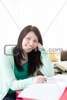 Smiling brunette student doing her homework