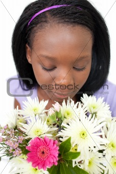 Charming young woman smelling flowers