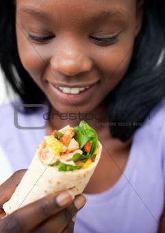 Afro-american young woman eating a wrap