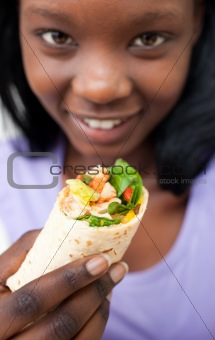 Charming young woman eating a wrap