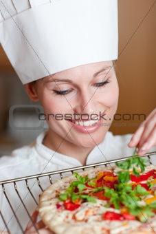 Beautiful female chef preparing a pizza