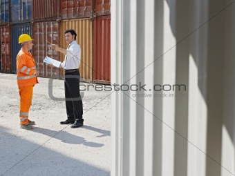 businessman and manual worker with cargo containers