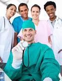 Smiling surgeon holding a stethoscope with his team in the backg