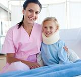 Smiling patient with a neck brace and her nurse in a hospital