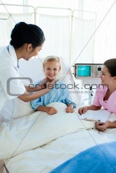 Attractive doctor examining a little female patient