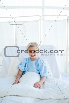 Smiling blond girl on a hospital bed