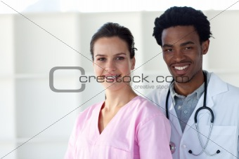 A doctor and a nurse smiling at the camera