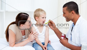 Mixed-race doctor giving some syrup to the little boy