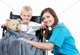 Nice female doctor carrying adorable little boy with his teddy b