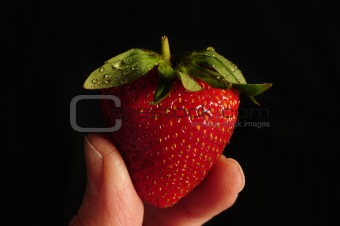 Single strawberry held between two fingers