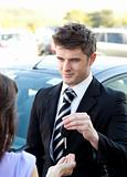 Young salesman giving car's key