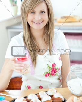 Attractive woman showing cakes in the kitchen