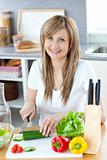 Delighted woman prapring a salad in the kitchen