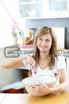 Cute woman preparing a cake in the kitchen