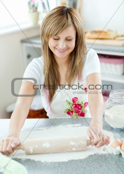 Caucasian woman preparing a cake in the kitchen at home